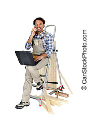 Carpenter perched on ladder whilst making a telephone call