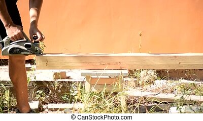 Carpenter planing a wooden beam with electric wood planer tool