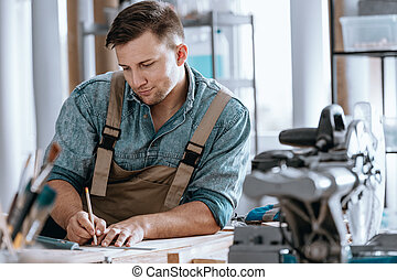 Carpenter planning work in workshop