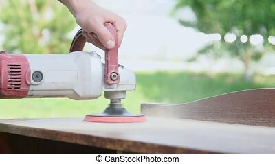 Carpenter polishing a wooden table with an electric sander in workshop closeup