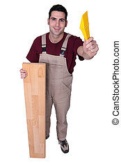 carpenter posing with floorboards and a float