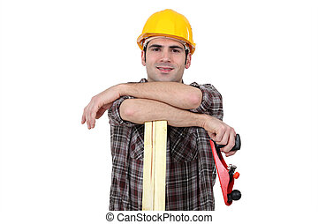 Carpenter posing with plank of wood and plane