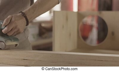 Carpenter process of wooden board by belt sander. Move forward and backward