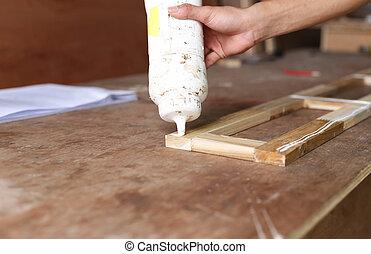 Carpenter putting glue on a piece of wood