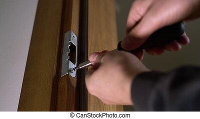Carpenter repairing door lock. Installing a door handle. Handyman tightening door hinge . Hands of the repairman with a screwdriver. Locksmith screwing bolt into wooden door