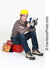 Carpenter sat on tool box with electric circular saw