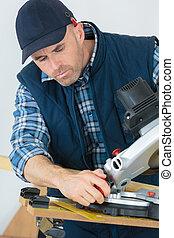 carpenter sawing a board on a machine