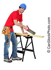 Carpenter sawing a piece of wood