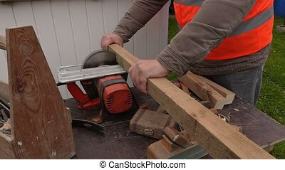 Carpenter sawing wooden plank with circular saw