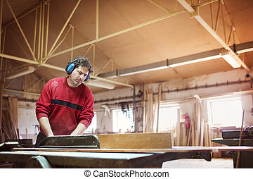 Carpenter sawing wooden planks - Carpenter cutting wooden...
