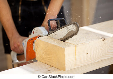 Carpenter saws a wood beam