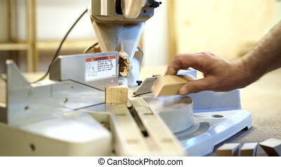 Carpenter saws wooden board on machine with circular saw. ...