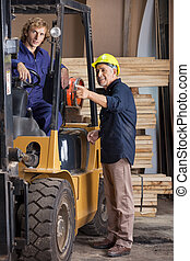 Carpenter Showing Something To Colleague In Forklift