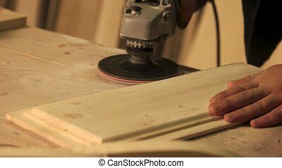 Carpenter smoothing plank with grinder.