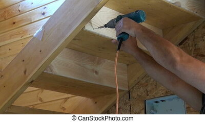 Impact Drill - Carpenter spins screws into a wooden board...