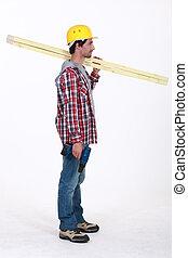 carpenter standing in profile holding ruler over his shoulder