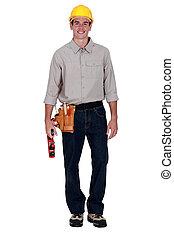 Carpenter stood holding wood plane
