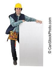 Carpenter stood with blank marketing panel