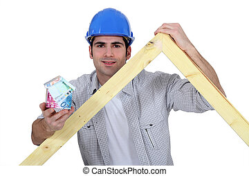 Carpenter stood with wooden truss and money