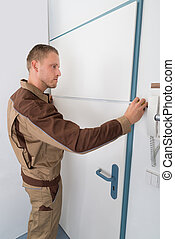 Carpenter Taking Measurement Of Door