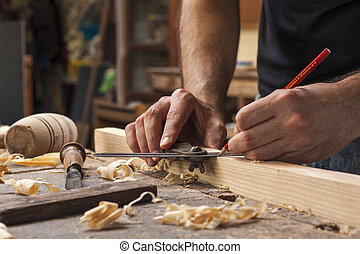 hand of a carpenter taking measurement of a wooden plank