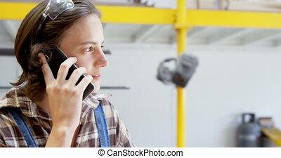 Carpenter talking on mobile phone in workshop 4k - Smiling ...