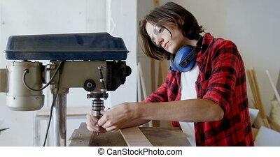 Carpenter tightening drill beat in vertical drill machine 4k...
