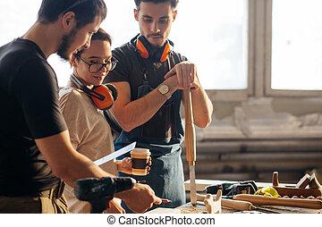 Carpenter Training Female Apprentice To Use Plane - Group of...