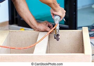 carpenter use air-gun for make new furniture