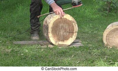 Carpenter uses handheld power sander to smooth sand oak tree...