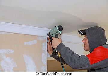 Carpenter using air nail gun to crown moldings trim for ceiling