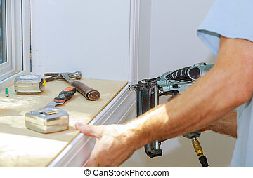 Carpenter using air nail gun to moldings for window - ...