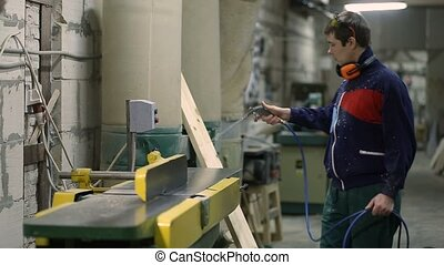 Carpenter using air nozzles gun to clean workplace -...