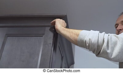 Carpenter using brad nail air gun to Crown Moulding on kitchen cabinets framing trim, with the all power tools