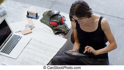 Carpenter using digital tablet while working on blueprint 4k...