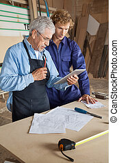 Senior carpenter using digital tablet with coworker in workshop