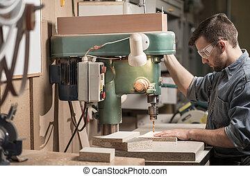 Carpenter using drill machine in the factory