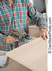 Carpenter Using Electric Drill In Workshop