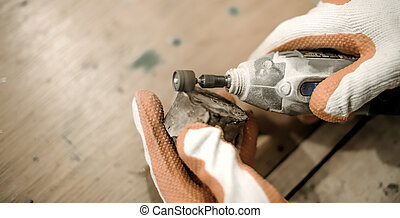 Carpenter using electric hand grinder