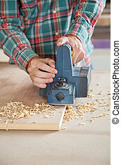 Carpenter Using Electric Planer On Plank
