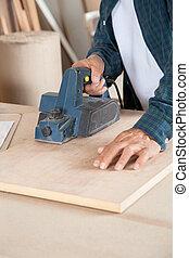 Carpenter Using Electric Planer On Wood