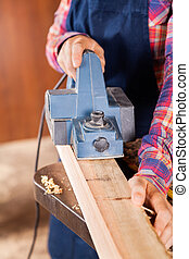 Carpenter Using Electric Planer On Wood
