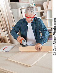 Carpenter Using Electric Sander At Table