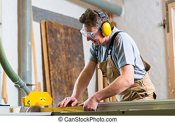 Carpenter using electric saw in carpentry - Carpenter...