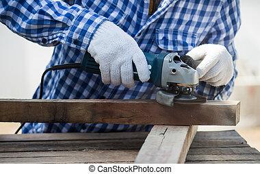 carpenter using grinder on wood