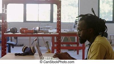 Carpenter using laptop at workshop 4k - Attentive carpenter...