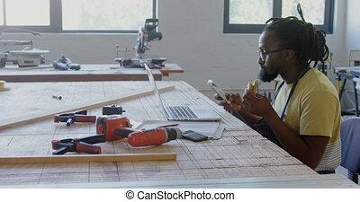 Carpenter using mobile phone and laptop while having breakfast 4k