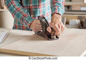 Carpenter Using Planer On Wood In Workshop
