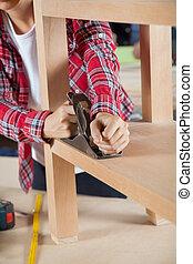 Carpenter Using Planer On Wooden Shelf