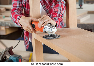 Carpenter Using Sander On Wood
